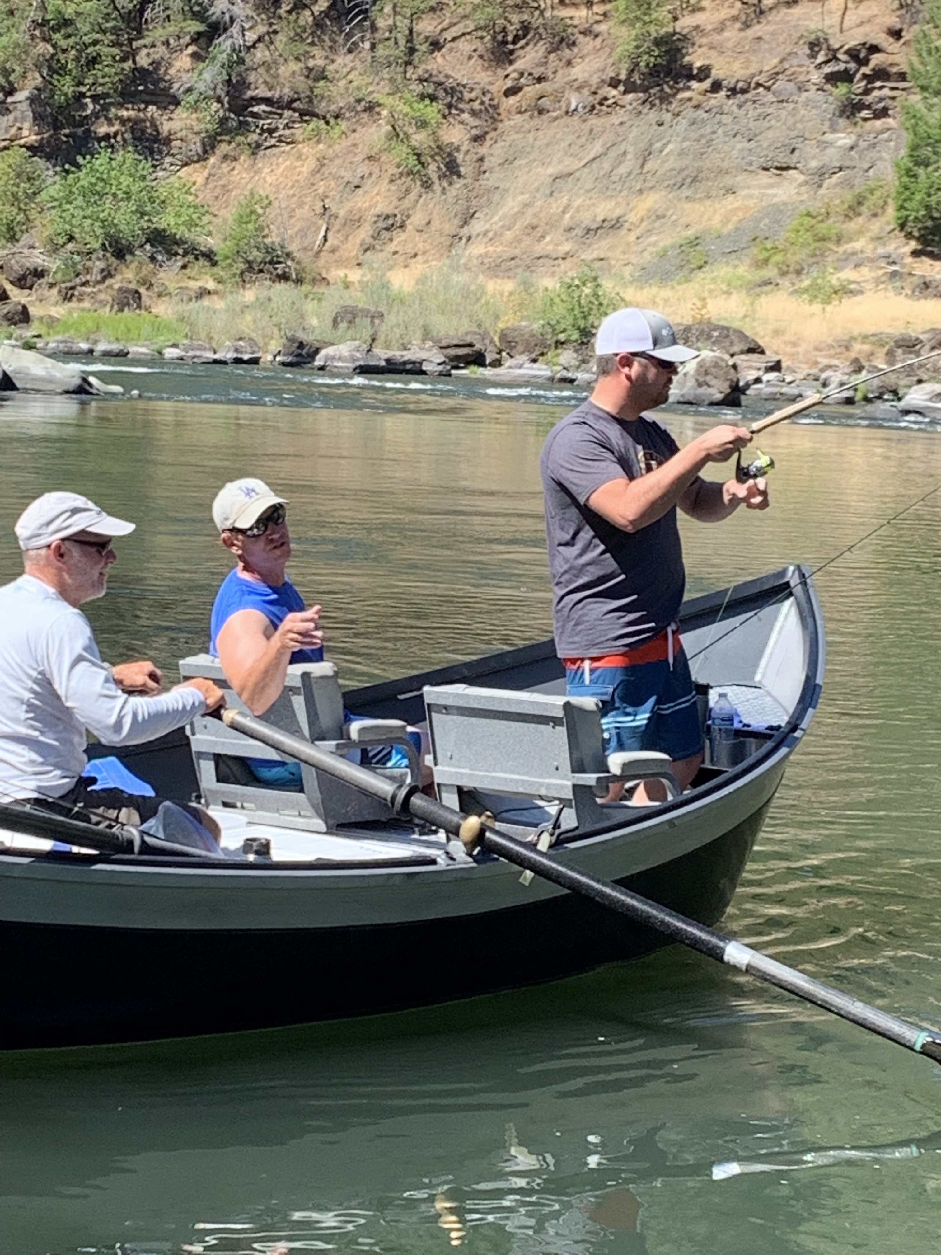 Fishing guide Dustin gives directions to staff while guest fishes on the Rogue River.