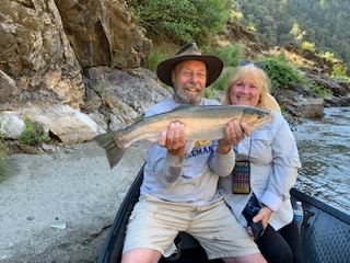Guests smile in delight at their catch of salmon on the Rogue River
